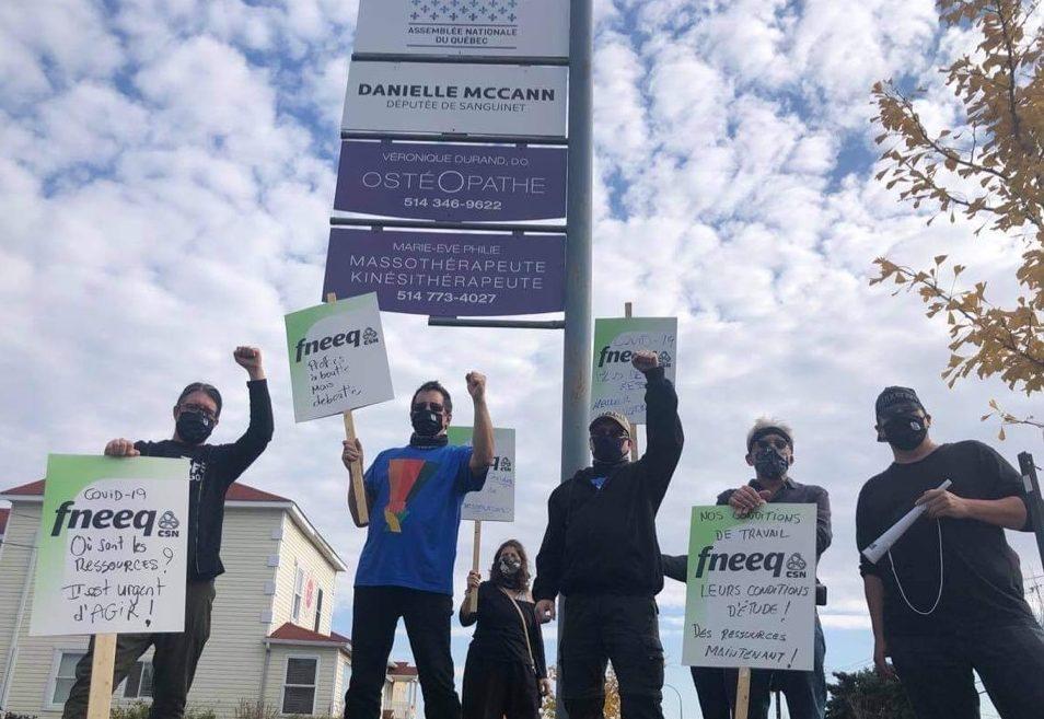 Des enseignants posent devant l'enseigne du bureau de la députée Danielle McCann pancartes à la main.