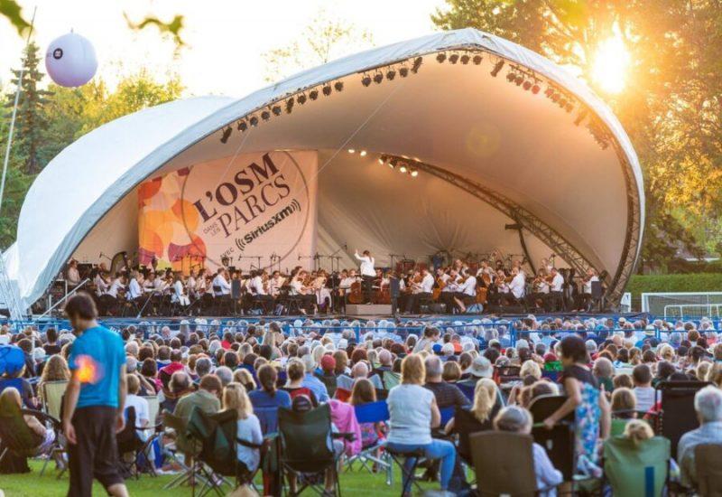 Des milliers de personnes assistent à un concert, les artistes sont sous un demi dôme en toile blanche.