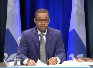 Lionel Carmant devant des drapeaux du Québec