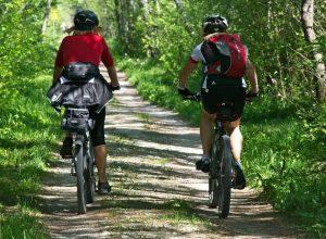 Deux cyclistes font du vélo sur une piste cyclable bordé d'arbres, ce qui inspirerait la trame verte de Beloeil.