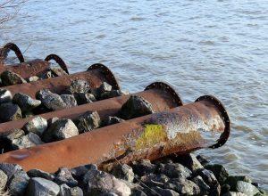 Des tuyaux de déversement d'eaux usées au-dessus d'un cours d'eau.