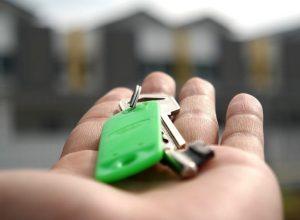 Une main tient des clés devant des maisons