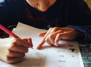 Un enfant, crayon à la main fait ses devoirs
