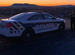 Une voiture de police du SPAL et une policère à ses côtés dans un coucher de soleil.