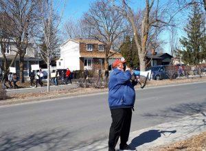 Un homme vêtu d'un manteau bleu parle dans un porte-voix alors qu'une centaine de personnes marchent derrière lui.